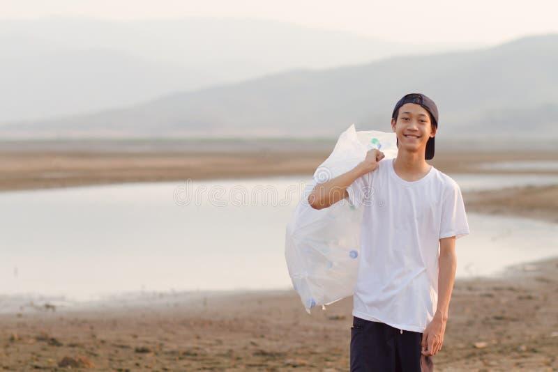 De vrijwilliger maakt rivier schoon opneemt plastiek en afval op grond royalty-vrije stock afbeeldingen