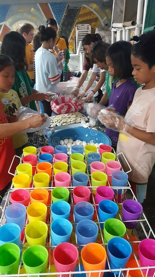 De vrijwilligers bereiden voedsel voor het voeden programma in een krottenwijkgemeenschap voor stock afbeeldingen