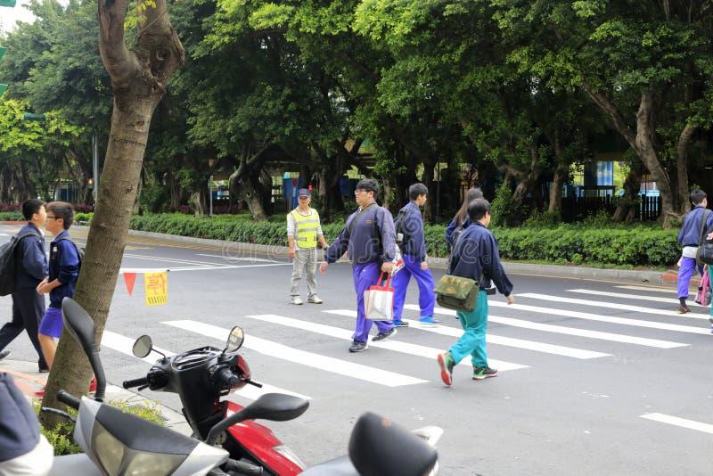 De vrijwilligers beschermen student die de weg kruisen royalty-vrije stock foto's