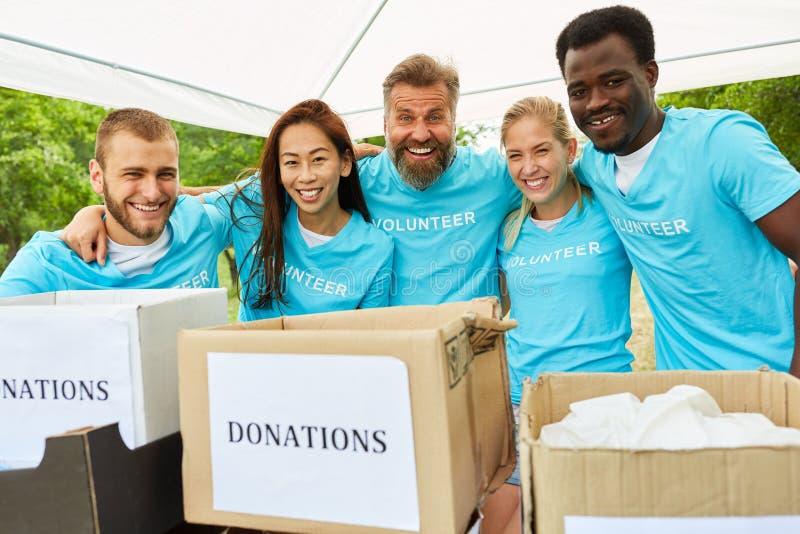 De vrijwilligers met schenkingsdozen zijn gelukkig stock afbeelding