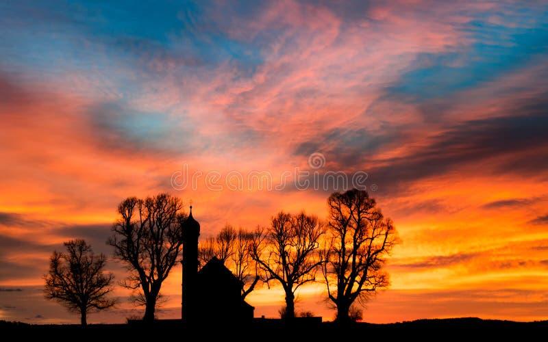 De vroege dageraad van de ochtendzonsopgang met silhouet kleine kerk of chape stock foto's