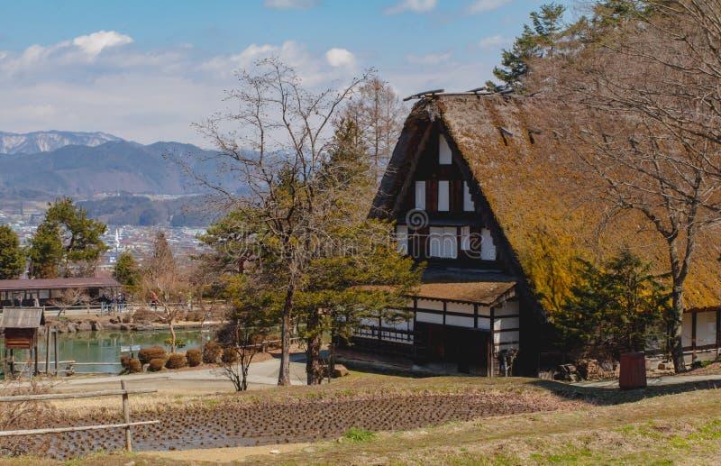 De vroege foto van het de lente toneellandschap van een traditioneel met stro bedekt dakhuis in Japan naast een padieveld stock afbeelding