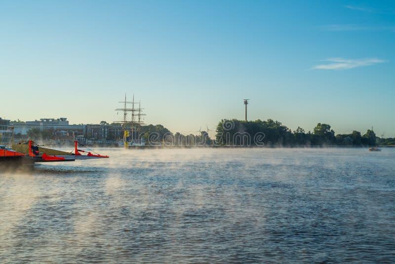 In de vroege ochtend, regelt een lichte mist op de rivier Weser in Bremen stock foto