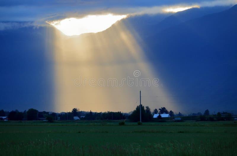 De vroege Stromen van het Ochtendzonlicht door Gebroken Wolk stock afbeelding