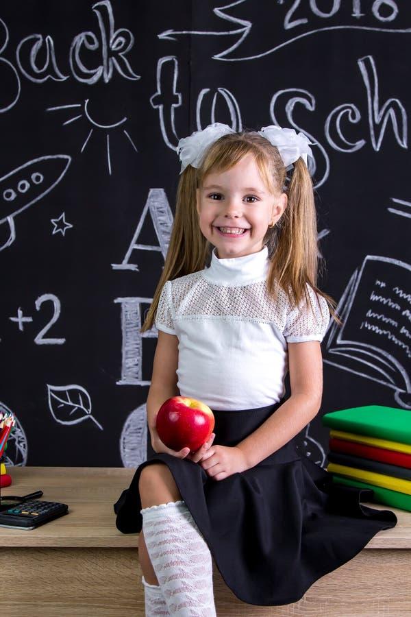 De vrolijk en het glimlachen schoolmeisjezitting op het bureau met boeken, school levert, holding een rode appel in de hand stock foto's