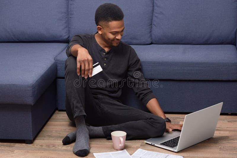 De vrolijke Afrikaanse Amerikaanse kerel houdt creditcard, controleert haar bankrekening op laptop computer, maakt online het win stock afbeelding