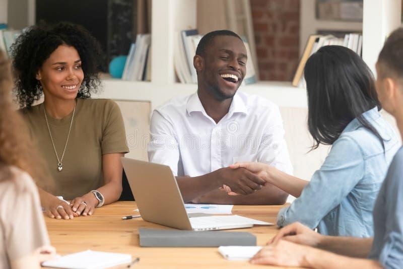 De vrolijke Afrikaanse partner van de zakenman schuddende hand op vergadering royalty-vrije stock foto