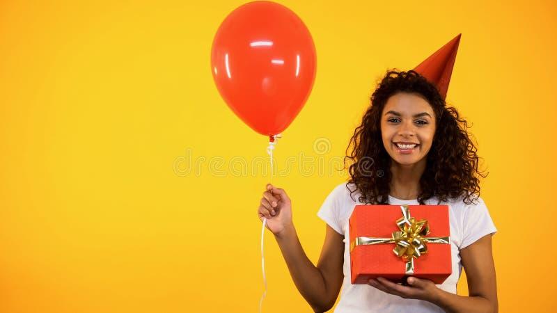 De vrolijke Afrikaanse vrouwelijke doos van de holdingsgift en ballon, vierende verjaardagspartij royalty-vrije stock afbeelding