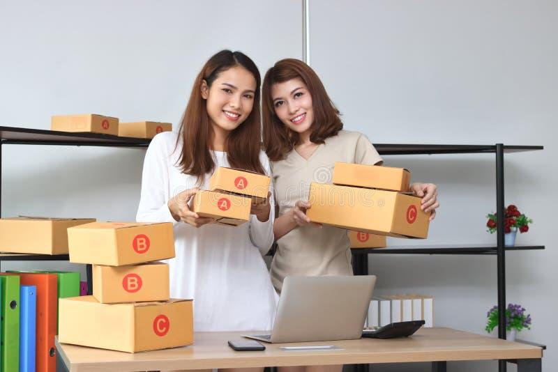 De vrolijke Aziatische vrouwen die van de ondernemerseigenaar zeker thuis bureau kijken Online startzaken stock foto