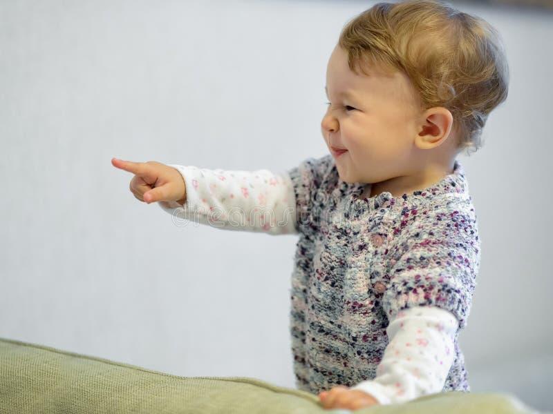 De vrolijke baby richt zijn vinger royalty-vrije stock afbeeldingen