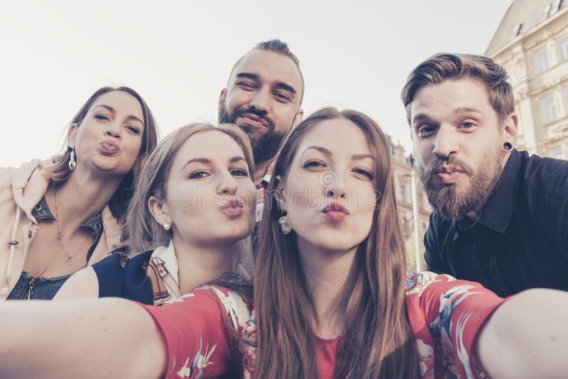 De vrolijke beste vrienden in de stad nemen een selfie die duckface kusuitdrukking maken stock afbeelding