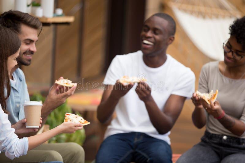 De vrolijke diverse studenten nemen een onderbreking etend pizza het drinken koffie royalty-vrije stock afbeeldingen