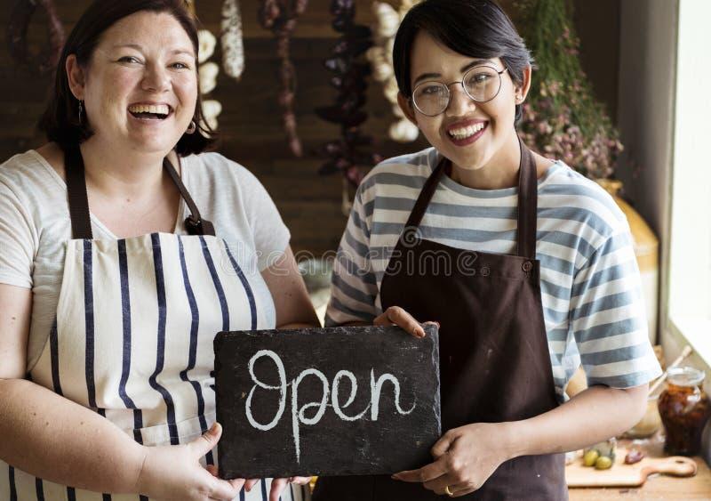 De vrolijke eigenaars die van de delicatessenwinkelwinkel een open teken tonen royalty-vrije stock foto