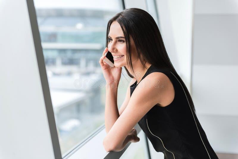 De vrolijke elegante dame spreekt op smartphone royalty-vrije stock afbeeldingen
