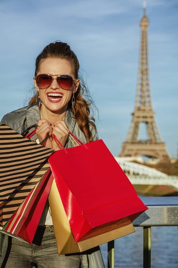 De vrolijke elegante vrouw met het winkelen doet dichtbij de toren van Eiffel in zakken royalty-vrije stock fotografie