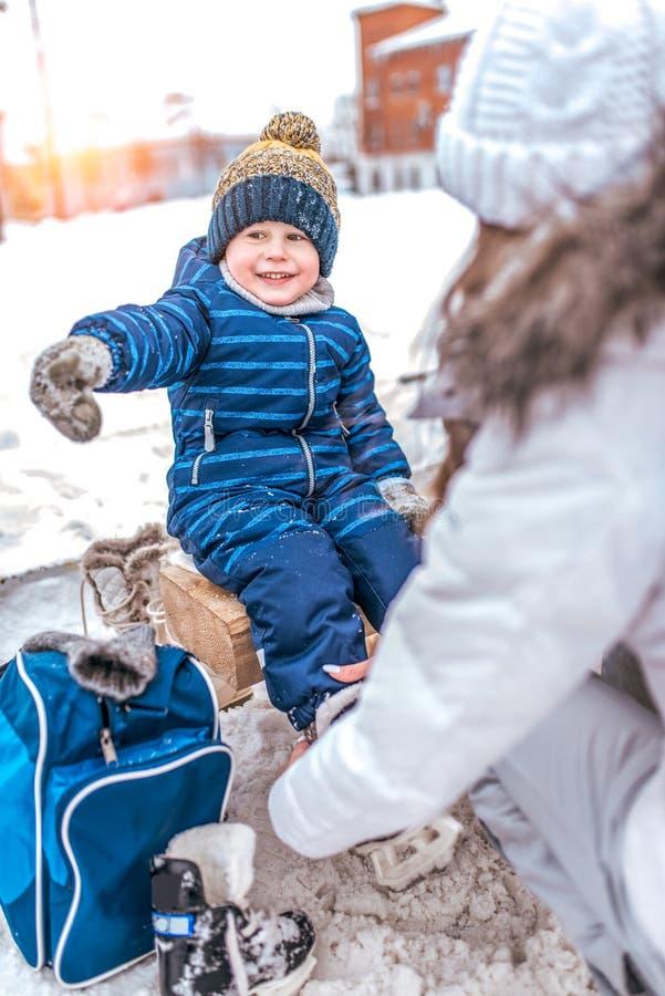 De vrolijke en blije jongen die van 4-6 jaar oud, op een bank, moeder zitten verandert schoenen in vleten Handgebaar van het kind stock foto's
