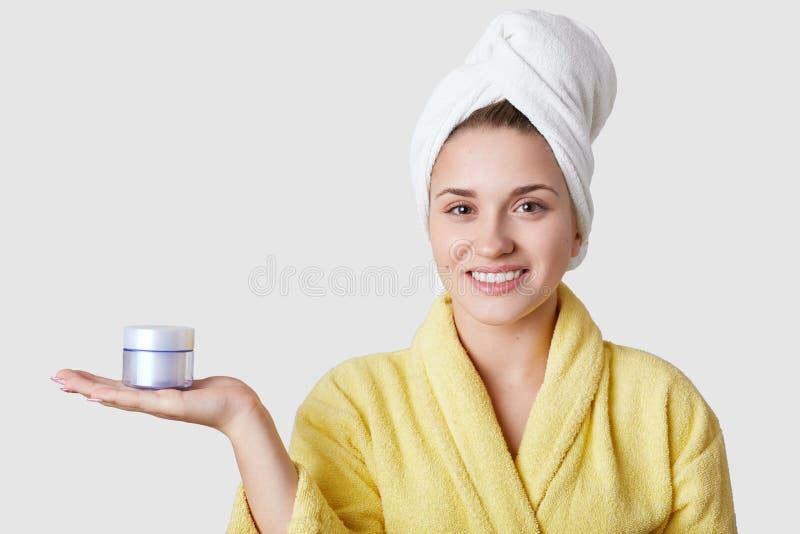 De vrolijke Europese vrouw draagt binnenlandse badjas en de handdoek, houdt anti het verouderen room, adverteert kosmetische binn royalty-vrije stock foto's