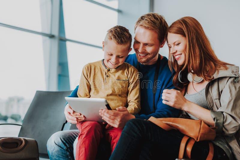 De vrolijke familie hangt uit met touchpad in hal stock foto