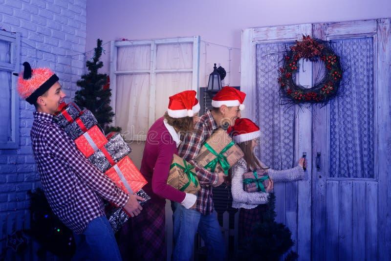 De vrolijke familie, in Kerstmanhoeden, gaat vrienden bezoeken stock foto