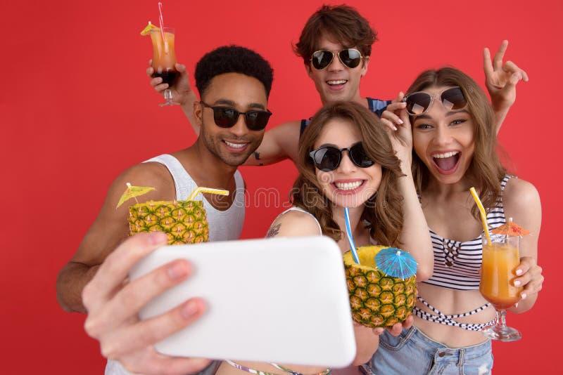 De vrolijke groep vrienden die cocktails drinken maakt selfie door phon stock foto