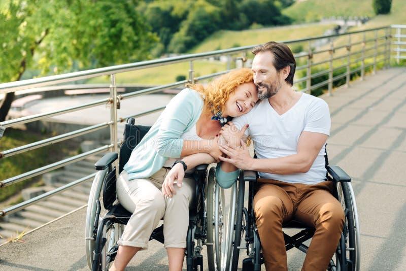De vrolijke hogere vrouw die haar het houden omhelzen van wheelchaired echtgenoot stock afbeeldingen