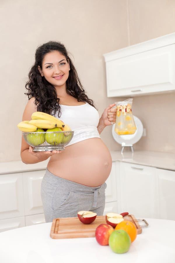 De vrolijke jonge aanstaande moeder bereidt a voor stock foto's