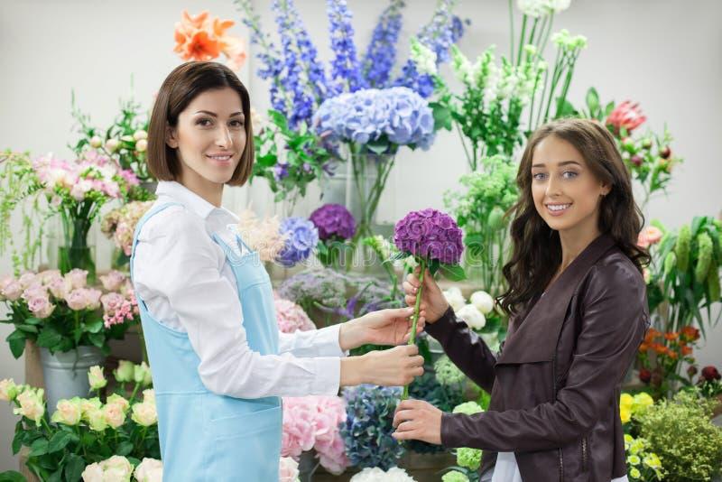 De vrolijke jonge bloemist dient haar klant royalty-vrije stock afbeelding