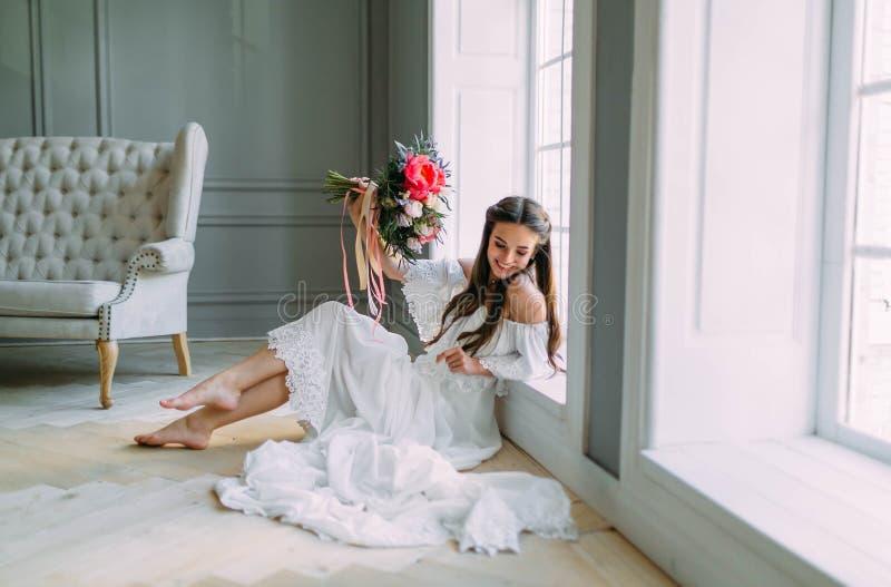 De vrolijke, jonge bruid houdt een rustiek huwelijksboeket met pioenen op panoramische vensterachtergrond De gelukkige jonge zakk royalty-vrije stock foto's