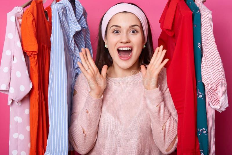 De vrolijke jonge dame spreidt palmen dichtbij gezicht uit en schreeuwt hooray De positieve vrouw houdt van nieuwe uitrusting Moo stock foto