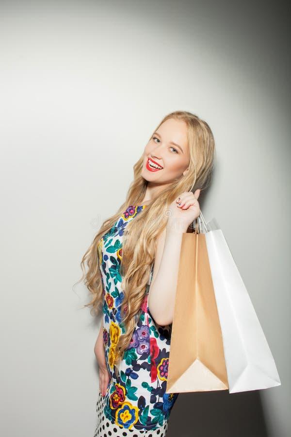 De vrolijke jonge gezonde vrouw is het gaande winkelen stock afbeelding