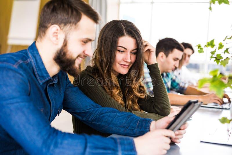 De vrolijke jonge groep freelancers werkt met vreugde in modern bureau Het bekijken telefoon en glimlach stock fotografie