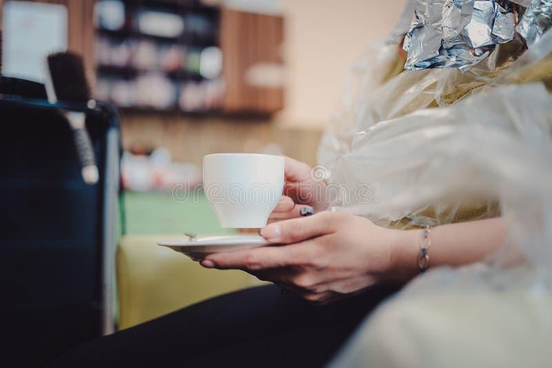 De vrolijke jonge kapper vlecht vrouwelijk haar De vrouw zit en drinkt thee of koffie royalty-vrije stock fotografie