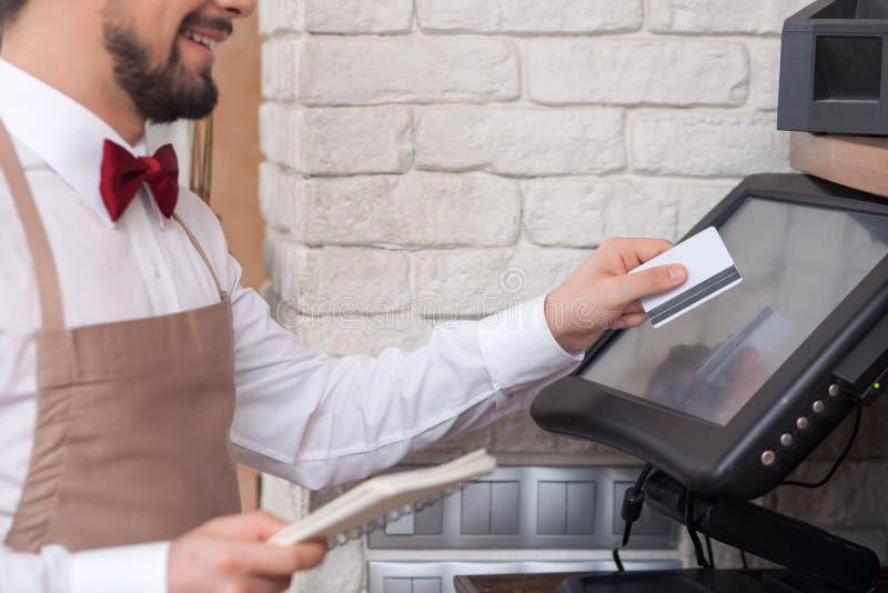 De vrolijke jonge kelner werkt met het controleren stock fotografie