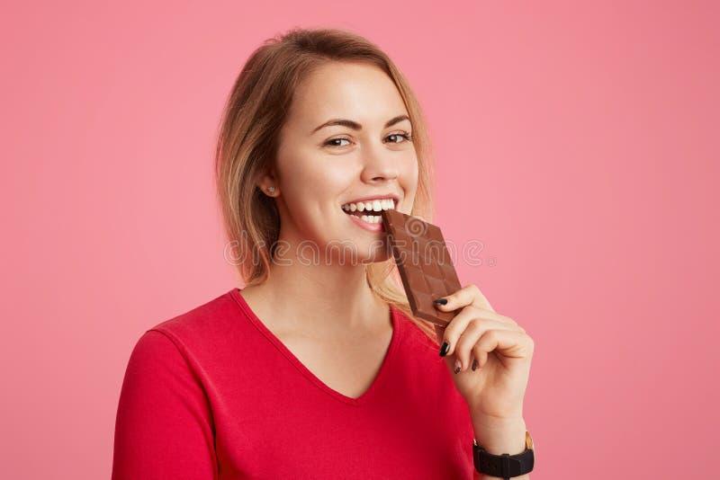 De vrolijke jonge mooie jonge vrouw geniet van zoete chocolade, doesn denkt ` t over cijfer, stelt het zijn in goede stemming zoa stock afbeeldingen