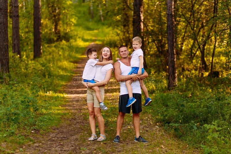 De vrolijke jonge ouders houden twee kinderen in openlucht in hun wapens in de zomer Familie royalty-vrije stock foto's