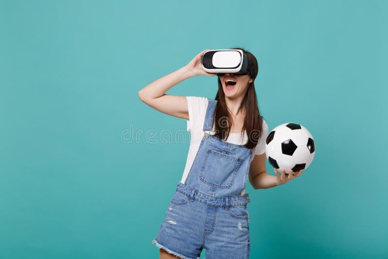 De vrolijke jonge ventilator die van de meisjesvoetbal in het voetbalbal van de hoofdtelefoonholding spelen kijkt geïsoleerd op b stock afbeelding