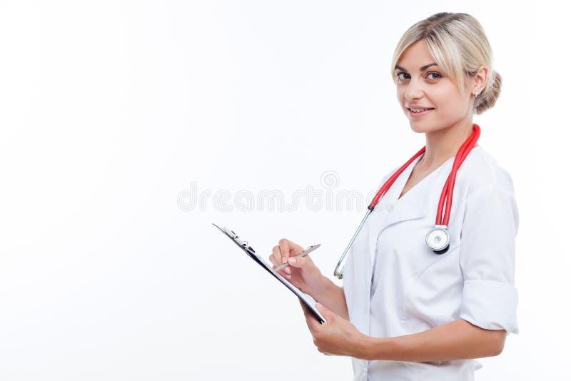 De vrolijke jonge vrouwelijke arts werkt met stock foto