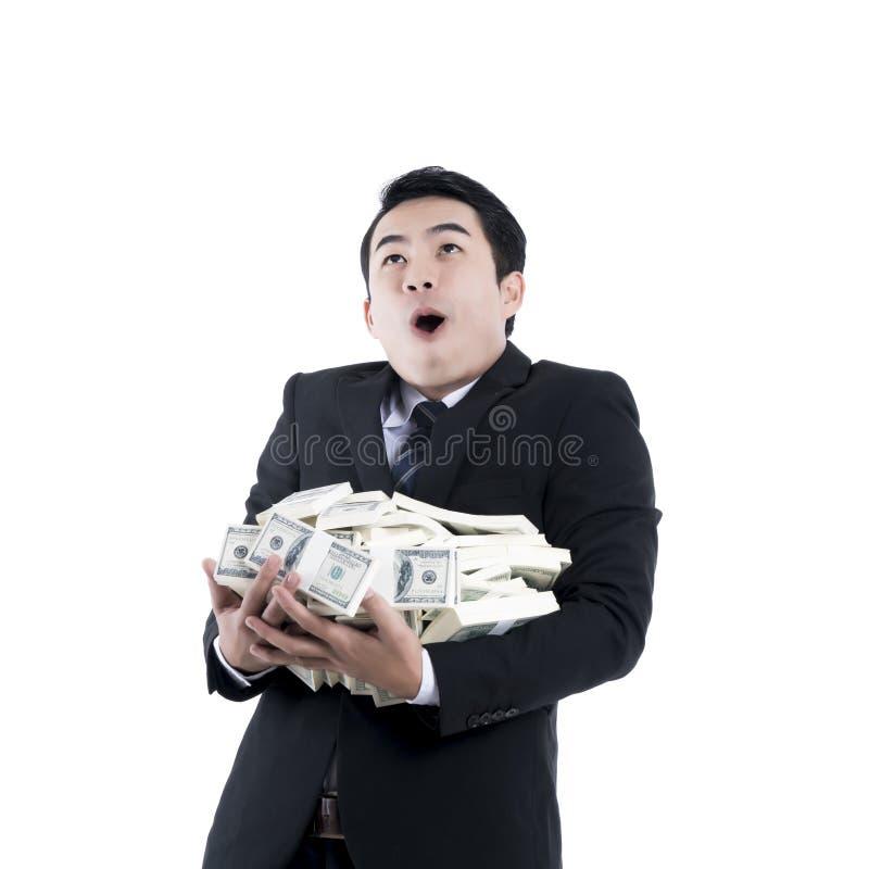 De vrolijke jonge zakenman die een grote stapel van geld houden in hallo royalty-vrije stock afbeelding