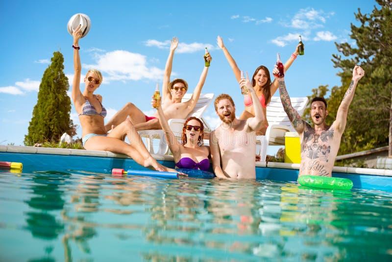 De vrolijke jongeren in pool verheugt zich met het opheffen van handen met bent royalty-vrije stock foto's