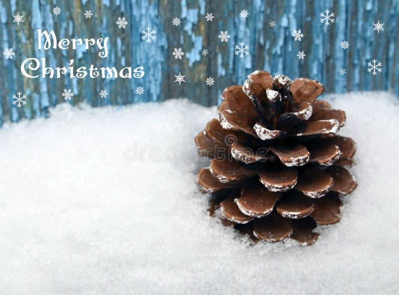 De vrolijke kaart van de Kerstmisgroet Feestelijke decoratie met denneappel op natuurlijke witte sneeuw en blauwe houten achtergr stock foto's