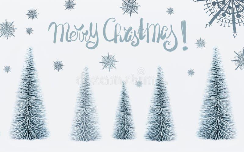 De vrolijke kaart van de Kerstmisgroet met tekst het van letters voorzien en decoratieve sparren bos en geschilderde sneeuwvlokke royalty-vrije stock fotografie