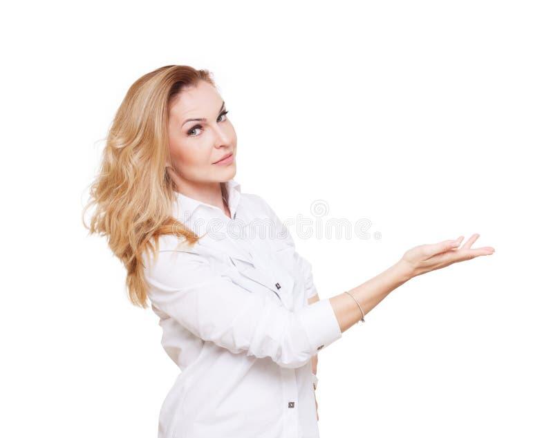 De vrolijke Kaukasische blonde vrouw toont iets geïsoleerd op witte achtergrond stock fotografie