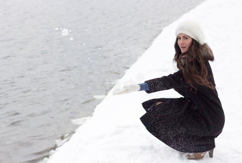 De vrolijke Kaukasische Jonge Vrouw in Sneeuwweer werpt snowbal stock foto