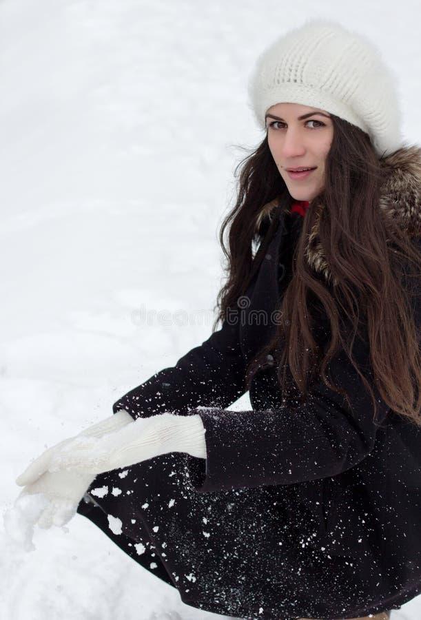 De vrolijke Kaukasische Vrouw in Sneeuwweer houdt in hand sneeuw stock fotografie