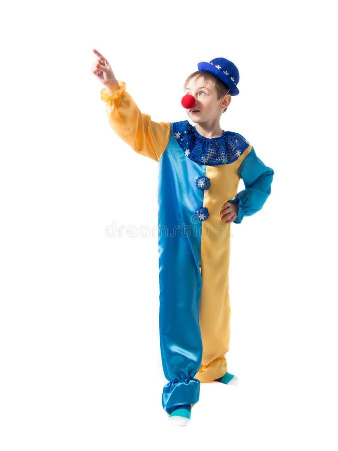 De vrolijke kind status in een clownkostuum met een blauwe hoed en toont zijn hand stock fotografie