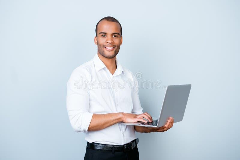 De vrolijke knappe jonge zwarte makelaar typt op zijn laptop, st royalty-vrije stock foto