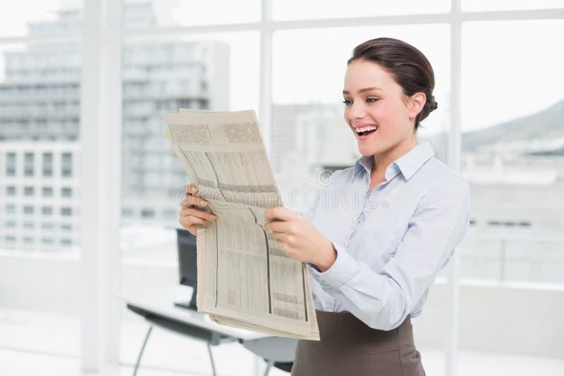 De vrolijke krant van de onderneemsterlezing in bureau stock foto