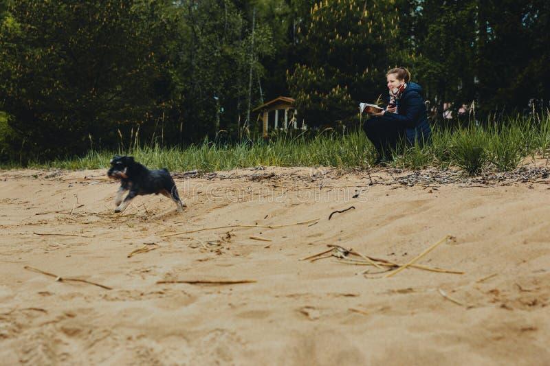 De vrolijke leuke jonge vrouw zit, leest boek en koestert haar hond op het strand Miniatuurschnauzer met de maitresse op het meer stock fotografie