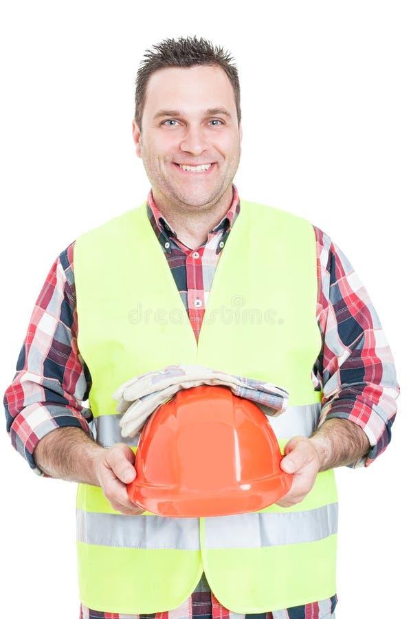 De vrolijke mannelijke helm en de handschoenen van de aannemersholding royalty-vrije stock fotografie