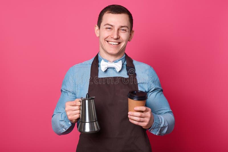 De vrolijke mannelijke kelner houdt koffiezetapparaat en document de kop, bereidt aardige drank voor bezoekers in koffie voor, he royalty-vrije stock afbeeldingen